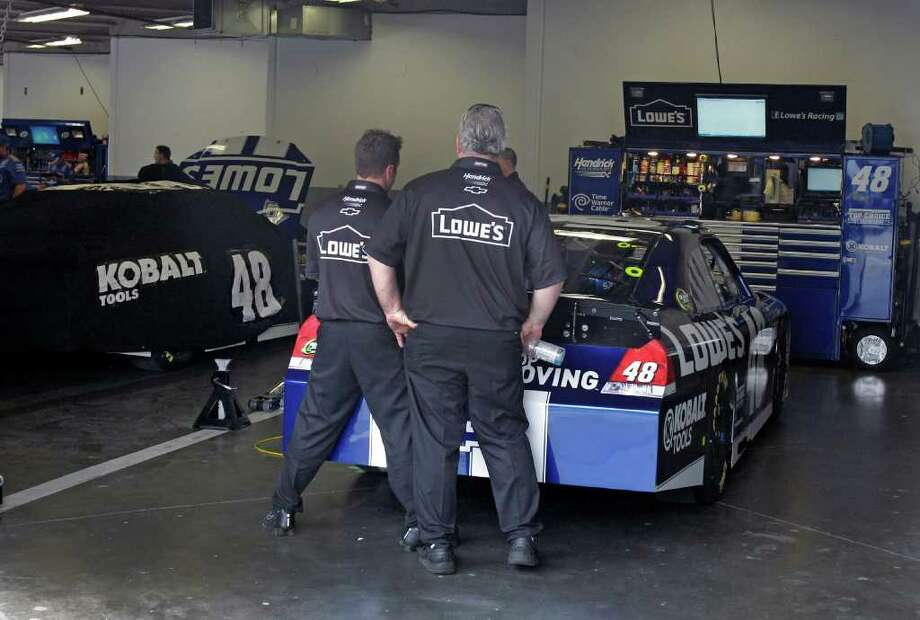 Jimmie Johnson's crew members work on his Budweiser Shootout car, while his Daytona 500 car (left) sits covered after it failed an inspection because of illegal modifications. Photo: AP
