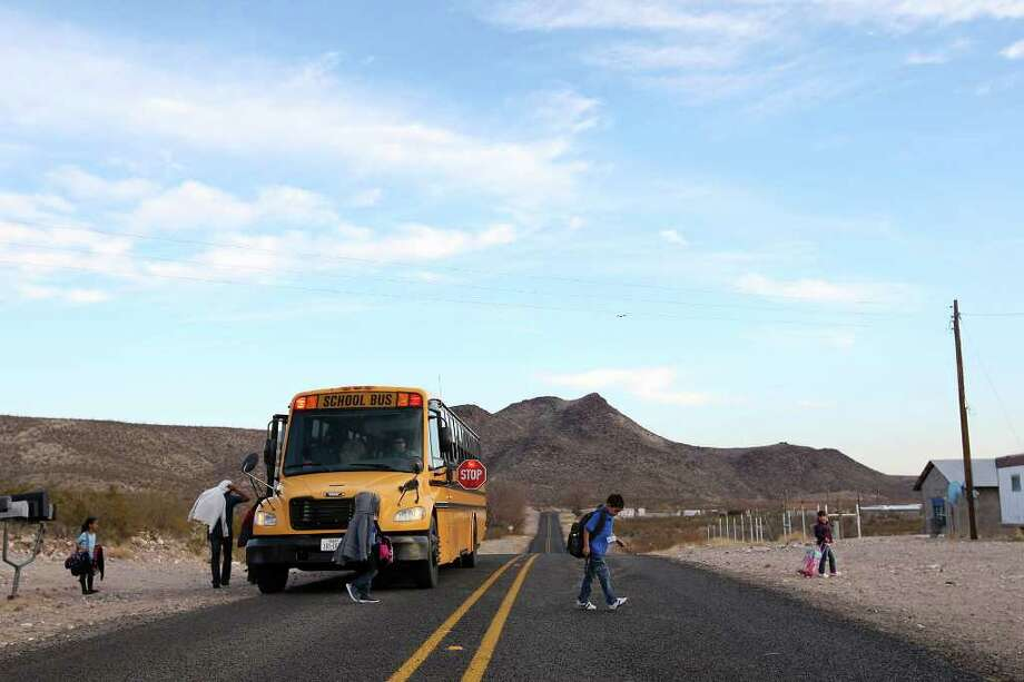 After a 50-mile ride, students are unloaded in Candelaria, Texas, Monday, Feb. 6, 2012. The town is located along the Rio Grande 42 miles southwest of Marfa, Texas. The Presidio County town lost its school in 1998 and students have since been bused over 50 miles to school in Presidio, Texas. Parent participation is at a minimal with the distance being a hardship. A Lutheran group is exploring the possibility of opening a charter school in the town. Photo: Jerry Lara, San Antonio Express-News / © San Antonio Express-News