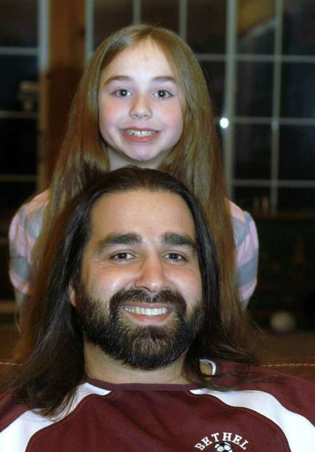 Nine-year-old Mia Prazeres and her father, Keith, of Bethel will both be donating the hair they have been growing for the past two years to the Pantene Beautiful Lengths program to be made into wigs for cancer patients. Photo: John Pirro