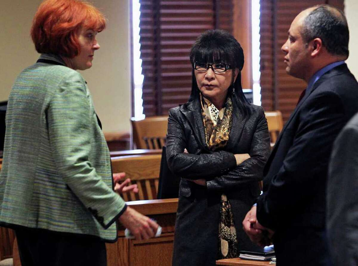 Tina Yuchnitz (center) talks with her attorney Stephani Walsh and Michael Yuchnitz's attorney Miguel Ortiz, during a break at the divorce trial of Mike and Tina Yuchnitz at the Bexar County Courthouse on Friday, Feb. 17, 2012.