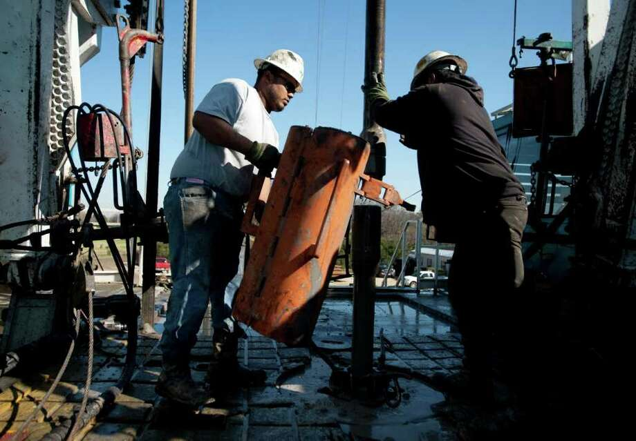 Toronto-based Trinidad Drilling Ltd. floorhands Julio Serrato, left, and Jaime Gonzalez work on the first drilling of the Reveille 1H Chesapeake Energy Corp. natural gas site near Fort Worth. Photo: Matt Nager