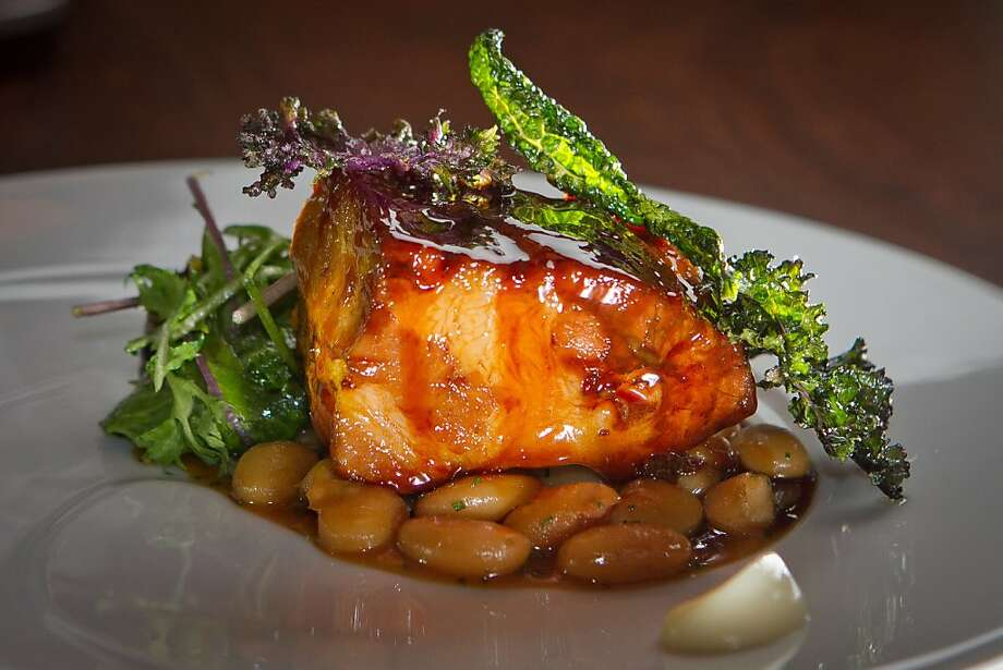 The slow-roasted pork has perfectly cooked beans, wine-infused cipollini onions and a Madeira sauce. Photo: John Storey, Special To The Chronicle