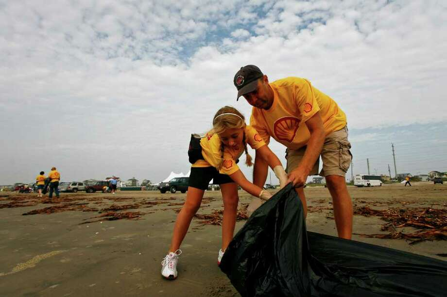 """Morgan and Danny Barnett, volunteers for Shell, help clean up the San Luis Pointe beachfront in Galveston during an """"Adopt-A-Beach"""" day. Photo: Michael Paulsen / Houston Chronicle"""