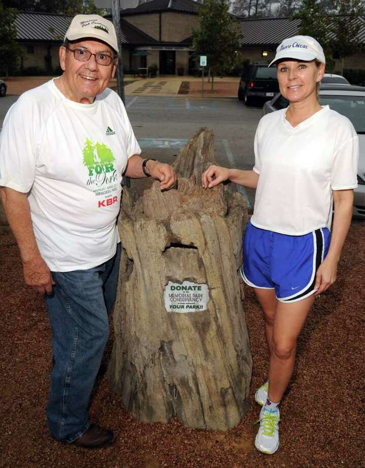 Memorial Park Conservancy board members John Paukune and Mindy Hildebrand created a faux tree stump bank for donations. Photo: Dave Rossman / © 2012 Dave Rossman