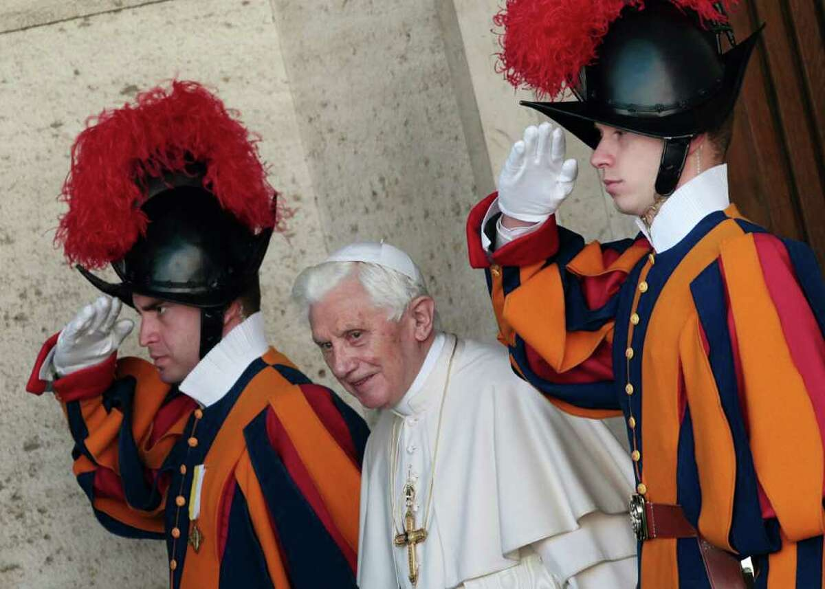 Pope Benedict XVI is saluted by Swiss guards as he leaves the Synod hall after a meeting with Cardinals and Bishops at the Vatican, Friday, Feb. 17, 2012. The Pontiff is scheduled to name 22 new Cardinals in a Consistory, Saturday Feb. 18, at the Vatican. (AP Photo/Gregorio Borgia)