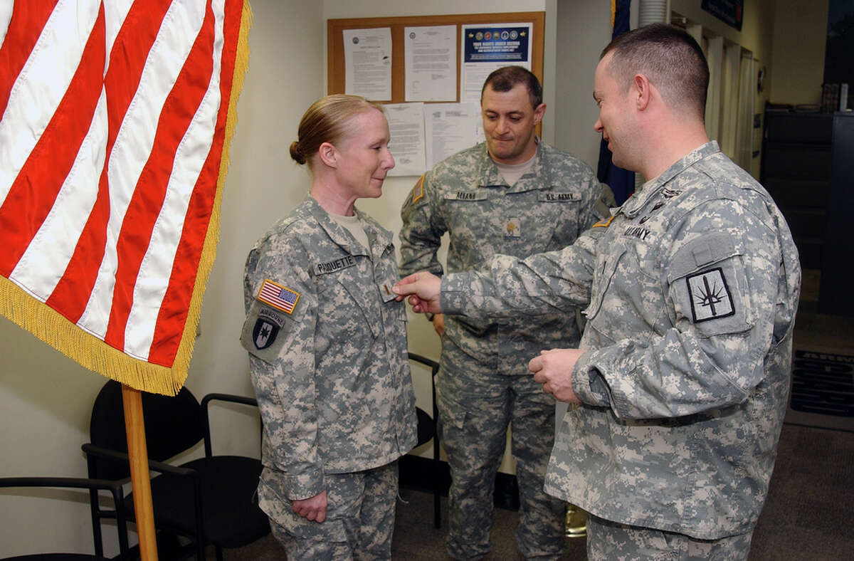 Sgt. 1st Class Steven Petibone, New York Army National Guard Tracy Pauquette of Granville receives her gold bar as a commissioned second lieutenant from Capt. John Klimes during a ceremony at the Watervliet Arsenal. Maj. Michael Alfano of Guilderland watches.