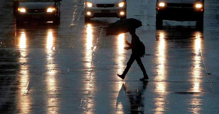 A pedestrian walks along San Jacinto as rain moves through Houston during rush hour on Friday evening. Photo: Mayra Beltran, Houston Chronicle / © 2012 Houston Chronicle