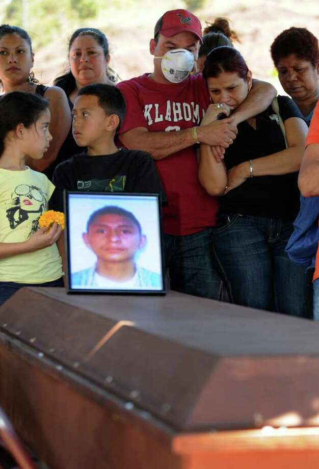 Relatives stand around the coffin of Marvin Javier Castro, 28, during his funeral at a cemetery in Tegucigalpa, Honduras, Friday February 17, 2012. Castro died along with hundreds of other inmates during a Feb. 15 fire at the prison in Comayagua. Photo: Fernando Antonio, Associated Press / AP