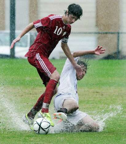 San Antonio Christian School  Anthony Kiser, right, slides on Grapevine Faith Christian Jonathan Orasanu during a downpour in the TAPPS Class 4A State Semifinal at Blossom Soccer Stadium.  Grapevine won 4-3. Friday, Feb. 17, 2012. Bob Owen/Express-News Photo: BOB OWEN, Express-News / © 2012 San Antonio Express-News