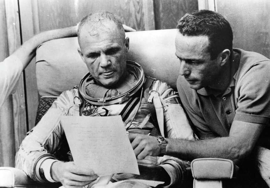 American astronaut Lt Col John Glenn checks over notes with back-up pilot Scott Carpenter after a simulated flight, prior to the Mercury-Atlas 6 mission at Cape Canaveral, the object of which is to put the first American spaceman into orbit around the Earth.  Original Publication: People Disc - HC0271 Photo: Keystone, Getty Images / Hulton Archive