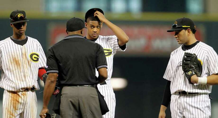 Grambling pitcher Matt Mitchell (4) listens to the umpire as he and his teammates meet on the mound during the 2nd inning of a college baseball game during the Urban Invitational at Minute Maid Park on Friday, Feb. 17, 2012. Photo: Karen Warren, Houston Chronicle / © 2012  Houston Chronicle