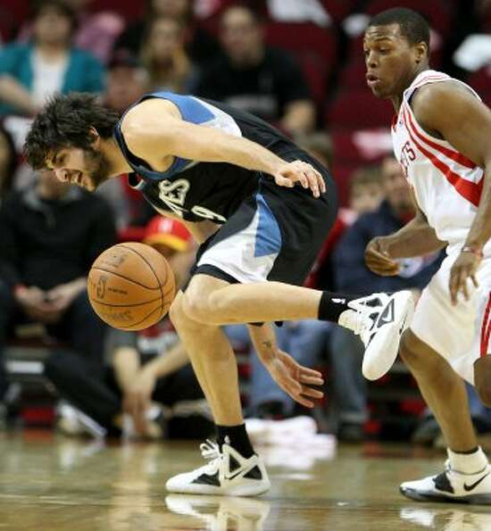 Minnesota's Ricky Rubio, left, tries to get a hand on a loose ball as Rockets guard Kyle Lowry gives