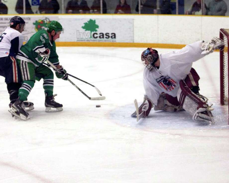 The Whalers' James Sanford battles for control of the puck in front of Delaware goalie Dan Meyers Friday night at the Danbury Arena. Photo: Barry Horn / The News-Times Freelance