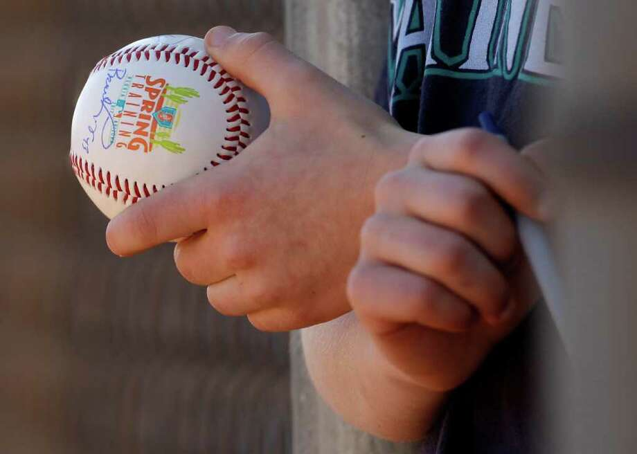 Riley Knies, 9, from Bellingham, Wash., holds a ball as he watches the Seattle Mariners during spring training baseball practice in Peoria, Ariz. Most fans dream of making at least one trek south to spend a week relaxing in the sun and watching their favorite teams. Photo: Charlie Riedel / AP