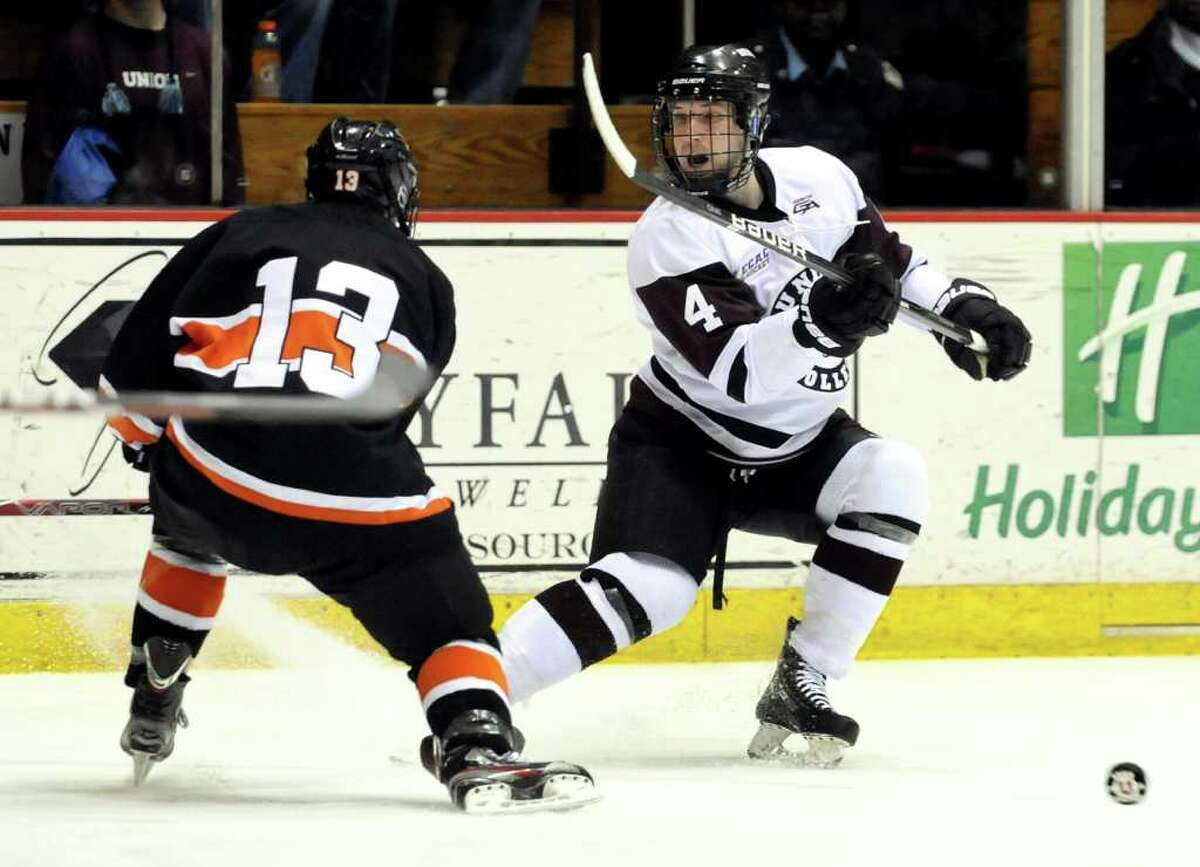 Union's Taylor Reid (4), right, pursues a puck that deflected off Princeton's Will Ford (13) during their hockey game on Friday, Feb. 17, 2012, at Union College in Schenectady, N.Y. (Cindy Schultz / Times Union)