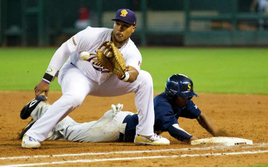 Prarie View first baseman Dominiq Harris, left, takes a throw as Southern's Demario Ellis dives back into the bag during The Urban Invitational college baseball round-robin tournament at Minute Maid Park Friday, Feb. 17, 2012, in Houston. Southern beat Prairie View 6-0. Photo: Brett Coomer, Houston Chronicle / © 2012 Houston Chronicle