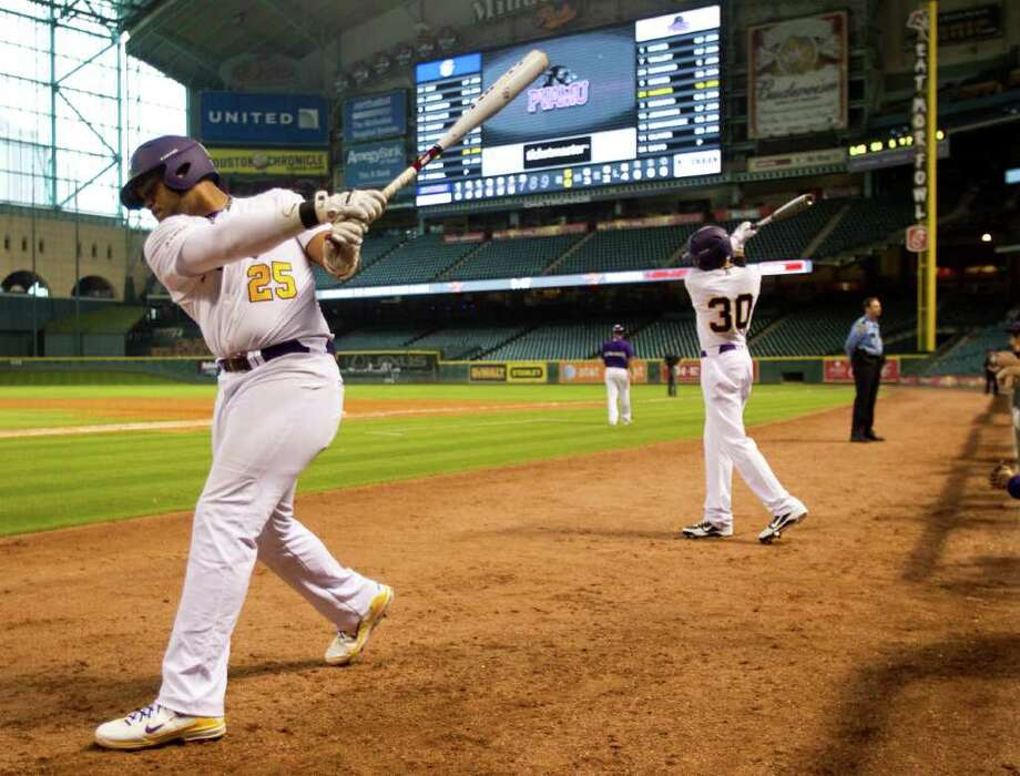 Prairie View first baseman Dominiq Harris (25) and outfielder Michael Long (3) warm up in the bottom half of the seventh inning against Southern University during The Urban Invitational college baseball round-robin tournament at Minute Maid Park Friday, Feb. 17, 2012, in Houston. Southern beat Prairie View 6-0. Photo: Brett Coomer, Houston Chronicle / © 2012 Houston Chronicle