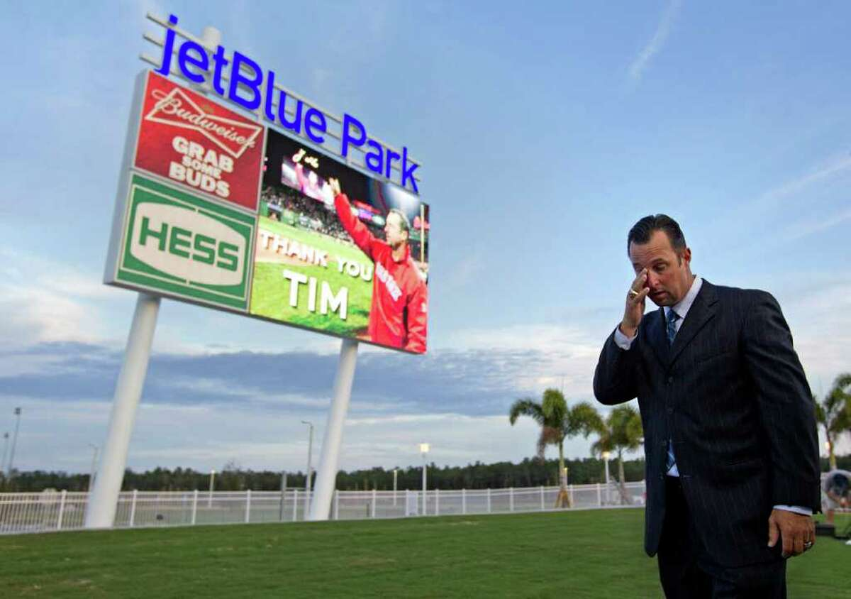 Boston Red Sox pitcher Tim Wakefield walks by a jumbotron displaying a dedication to him after announcing his retirement during a news conference at the Red Sox's baseball spring training complex Friday, Feb. 17, 2012, in Fort Myers, Fla. (AP Photo/David Goldman)