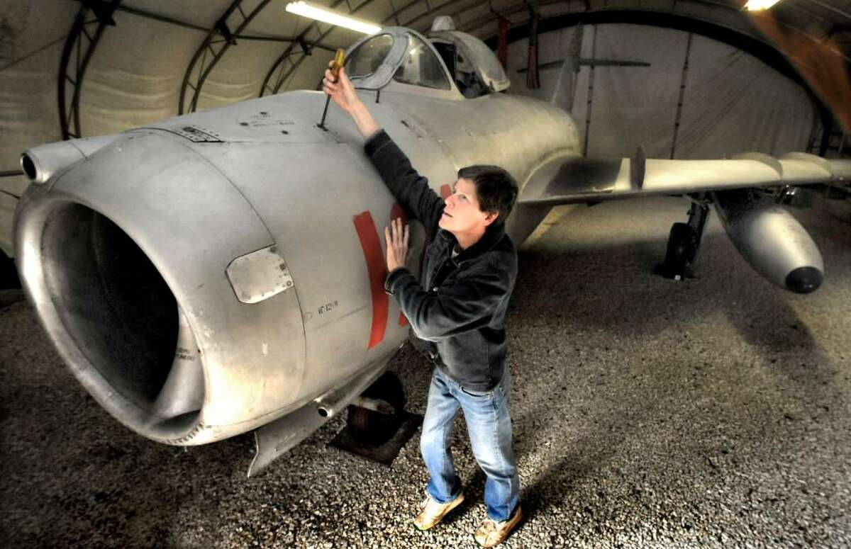 Lynn Brown, opens an inspection panel on a MiG-17, high-subsonic performance jet fighter, made in the USSR, in 1958, in the Hanger, at her Danbury home, on Monday, Nov.2,2009.