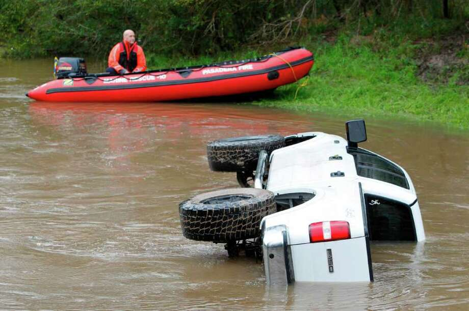 Pasadena Fire Department Marine Rescue and Houston Police Diving Team investigated a submerged vehicle found in a small bayou in the 5500 block of Genoa Red Bluff Road on Saturday in Pasadena. Photo: Mayra Beltran, Houston Chronicle / © 2012 Houston Chronicle