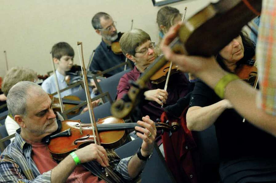 Laurence Sugarman of Rochester,left, participates in a Basics of Fiddle Technique workshop as part o