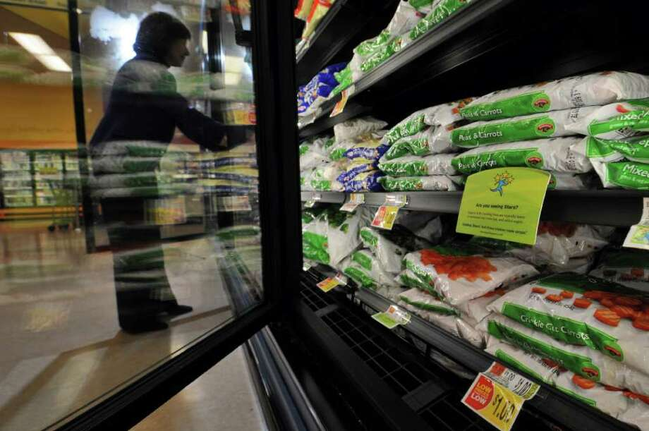 Hannaford Supermarkets Nutrition Coordinator Marianne Romano looks through a frozen vegetable case at the Wolf Road store, as local supermarkets try to encourage healthy eating, on Monday Feb. 14, 2012 in Colonie, NY.  (Philip Kamrass / Times Union ) Photo: Philip Kamrass / 00016349A