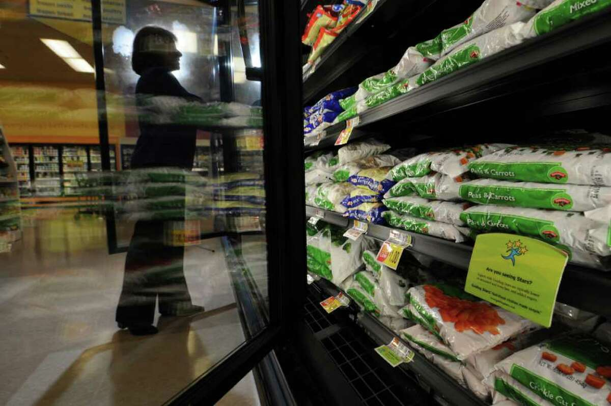 Hannaford Supermarkets Nutrition Coordinator Marianne Romano looks through a frozen vegetable case at the Wolf Road store, as local supermarkets try to encourage healthy eating, on Monday Feb. 14, 2012 in Colonie, NY. (Philip Kamrass / Times Union )