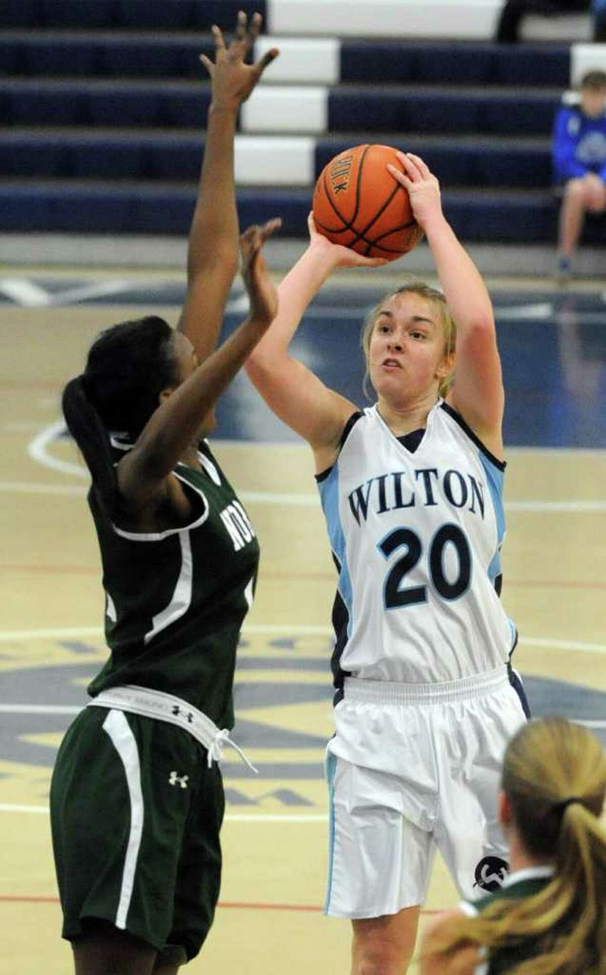 Wilton's Maddy Fulton takes a shot as she is defended by Norwalk's Emma Oyomba during Saturday's FCIAC Girls Basketball quarterfinal game at Wilton High School on February 18, 2012.