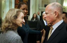 Jerry Brown, governor of California, right, speaks with Secretary of State Debra Bowen after giving the State of the State address at the state assembly in Sacramento, California, U.S., on Wednesday, Jan. 18, 2012. Brown reaffirmed support for a $98.5 billion high-speed passenger rail system and an $12 billion effort to improve the most populous state's water supply. Photographer: Ken James/Bloomberg *** Local Caption *** Jerry Brown; Debra Bowen