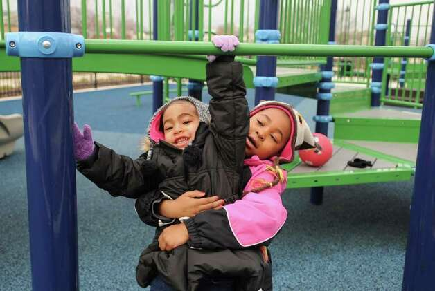 Zoe Bates, 3, gets a lift from her sister, Aniya, 6, as they play at Commons Park in Harbor Point in Stamford on Saturday, February 18, 2012. Photo: Lindsay Niegelberg / Stamford Advocate