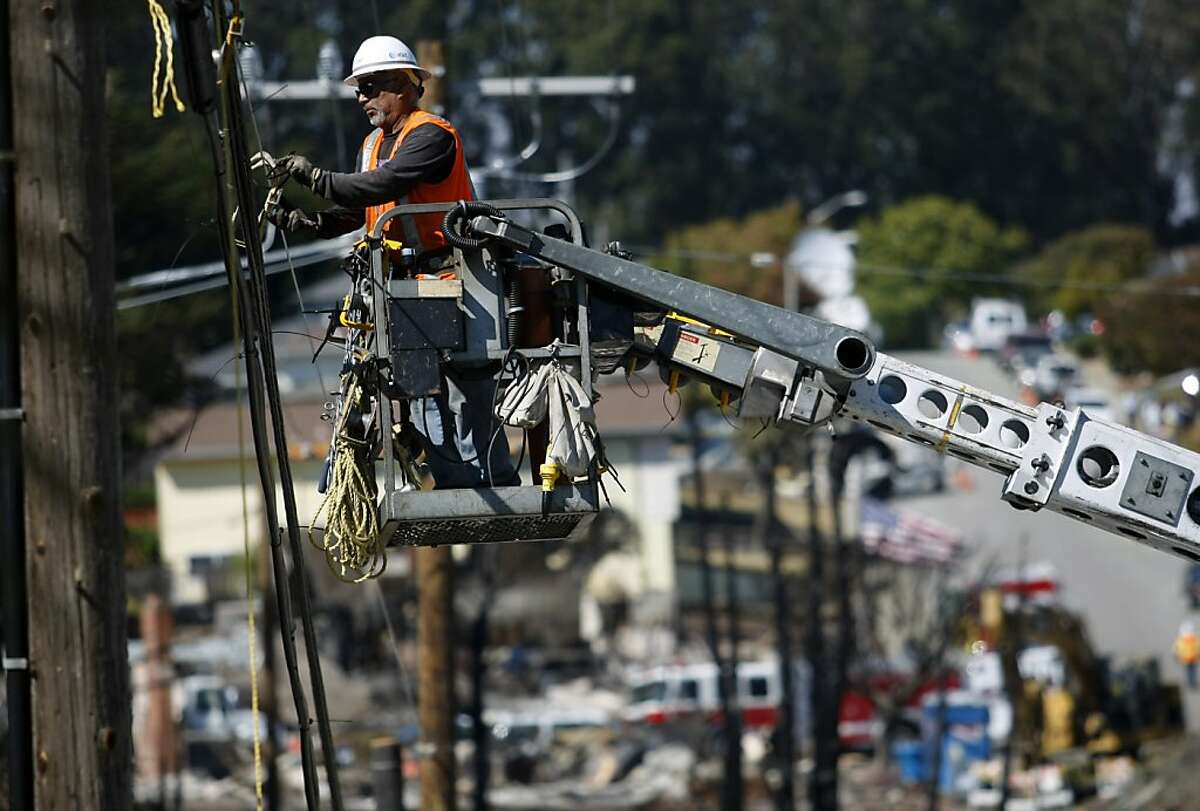 In this file photo, Louie Rocha Jr. prepares lines for new telephone wire for AT&T in San Bruno, Calif.