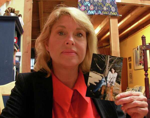 Heidi Hutchinson, older sister of Gina R. Hutchinson, holds a photo of her late sister. (James M. Odato / Albany Times Union) Photo: James M. Odato