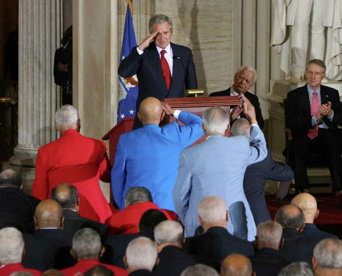 President Bush salutes the Tuskegee Airmen at the end of his speech and several in the front row stand to salute him back. The President received a standing ovation when he took the podium on Thursday, March 29, 2007 on Capitol Hill in Washington. The Tuskegee Airmen were awarded the Congressional Gold Medal Ceremony in the Rotunda of the U.S. Capitol. (Lauren Victoria Burke for The Times Union)