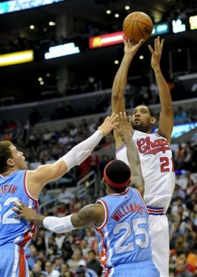 San Antonio Spurs center Tim Duncan (21) shoots for a basket over Los Angeles Clippers forward Blake Griffin, front left, and guard Mo Williams (25) during the first half of an NBA basketball game, Saturday, Feb. 18, 2012, in Los Angeles. (AP Photo/Gus Ruelas) (AP)