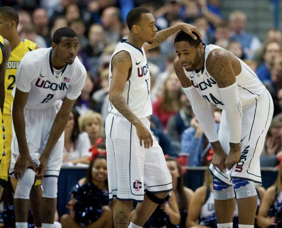 Connecticut's Ryan Boatright, center, Alex Oriakhi, right, and DeAndre Daniels, left, react after a foul against Connecticut in the first half of an NCAA college basketball game in Hartford, Conn., Saturday, Feb. 18, 2012.  (AP Photo/Jessica Hill) Photo: Jessica Hill, Associated Press / AP2012