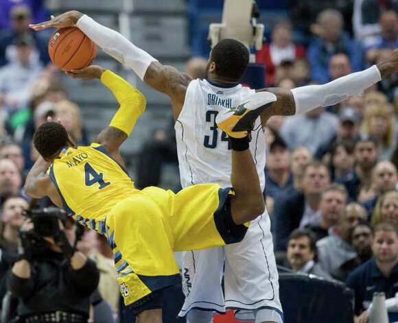 Connecticut's Alex Oriakhi, right, fouls Marquette's Todd Mayo during the first half of an NCAA college basketball game in Hartford, Conn., Saturday, Feb. 18, 2012.  (AP Photo/Jessica Hill) Photo: Jessica Hill, Associated Press / AP2012