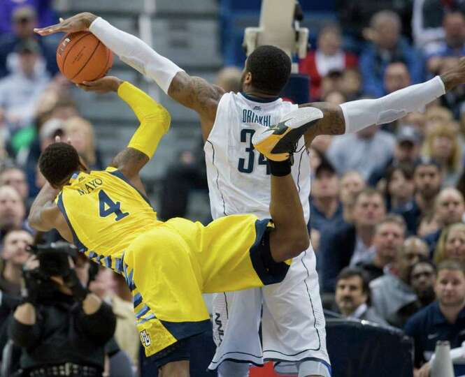 Connecticut's Alex Oriakhi, right, fouls Marquette's Todd Mayo during the first half of an NCAA coll