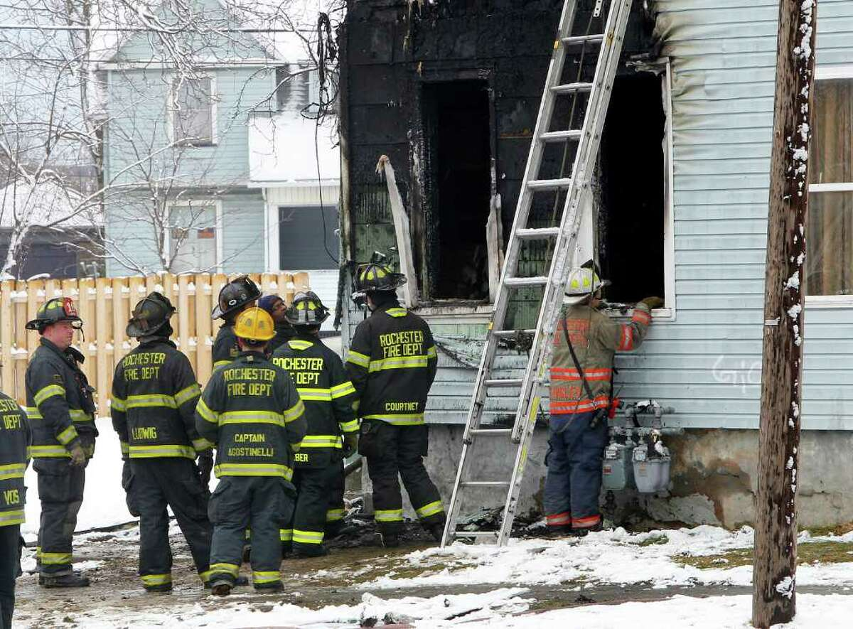 Rochester Fire Department officials work at the scene of a fire in Rochester, N.Y. on Saturday, Feb. 18, 2012. A fast-moving fire swept through the multifamily home early Saturday, killing four people, all of whom appeared to be children or teenagers, fire officials said. (AP Photo/Democrat & Chronicle, Kris J. Murante)