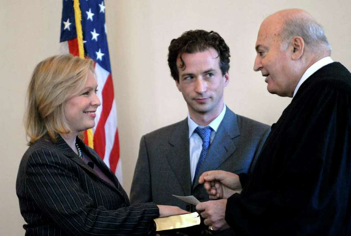 Rep. Kirsten Gillibrand takes the oath of office to serve in the 110th Congress on Tuesday, Jan. 2, 2007, at the Columbia County Courthouse in Hudson. Federal Court of Appeals Judge Roger Miner and her husband, Jonathan Gillibrand, center, take part in the ceremony. (Cindy Schultz / Times Union)