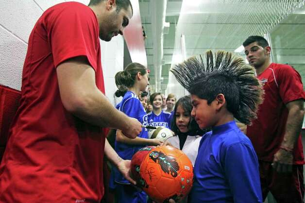 John-Anthony Coronado and his extreme hairstyle lead a line of fans who gathered off the field for autographs at the Scorpions' first practice, which was brought inside because of heavy rain. Photo: TOM REEL, Express-News / San Antonio Express-News