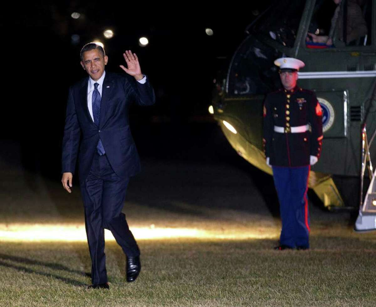 President Barack Obama waves as he walks across the South Lawn of the White House after stepping off Marine One helicopter during his arrival in Washington, early Saturday, Feb., 18, 2012. (AP Photo/Pablo Martinez Monsivais)