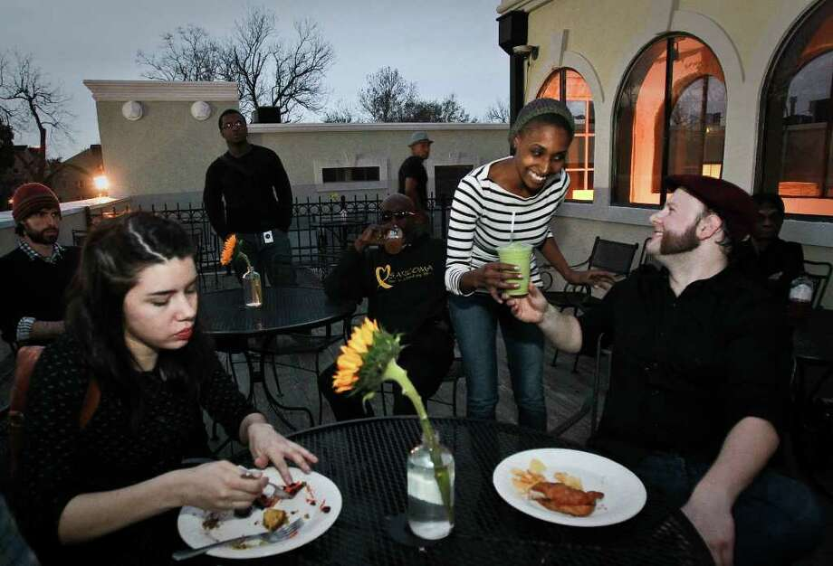 Danielle Fanfair, co-curator of Eat Gallery, gives Joshua Aplebee a smoothie made by one of the restaurant's volunteers. Eat Gallery showcases cooks and entrepreneurs who hope to gain exposure and start their own businesses. Photo: Nick De La Torre / © 2012  Houston Chronicle