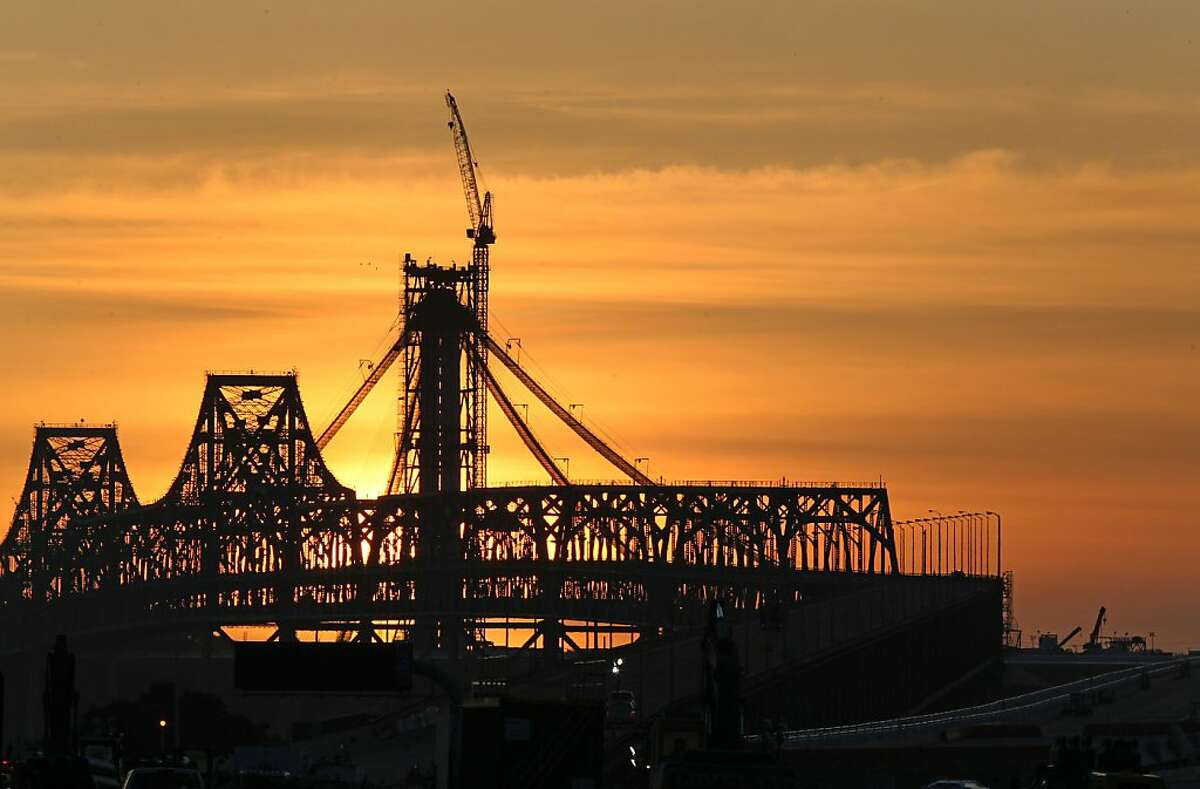 The old boxed steel frame of the Bay Bridge is silhouetted against San Francisco's sunset Saturday, February 18, 2012.