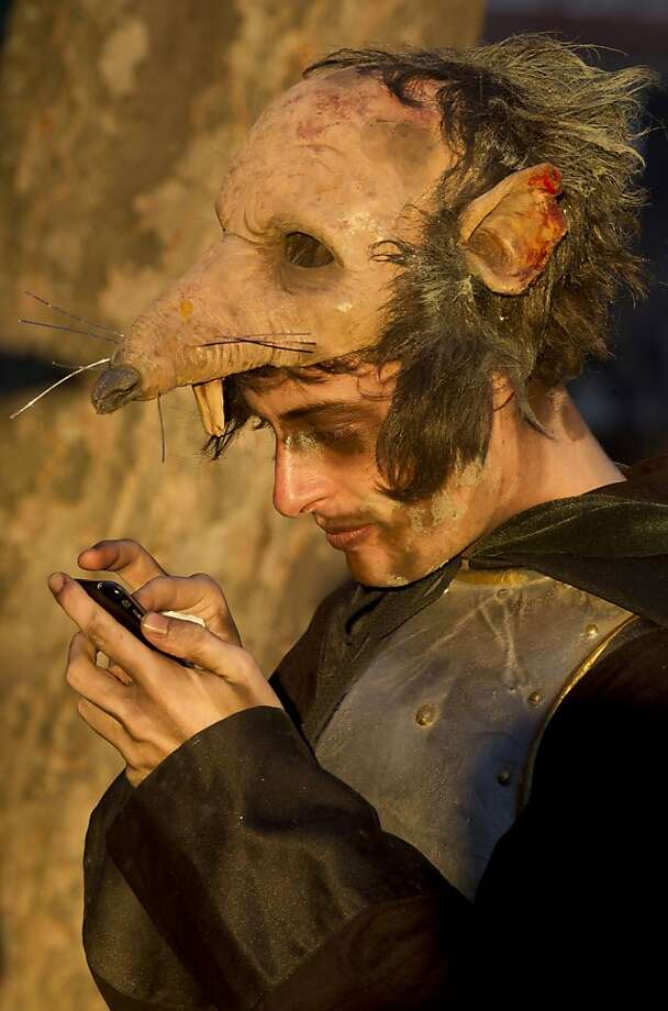 A reveler checks his cell phone before carnival celebrations in Madrid Saturday, Feb. 18, 2012.  The Carnival, which takes place across Spain just before Lent, is believed to owe its origins to pagan festivals. Photo: Paul White, Associated Press