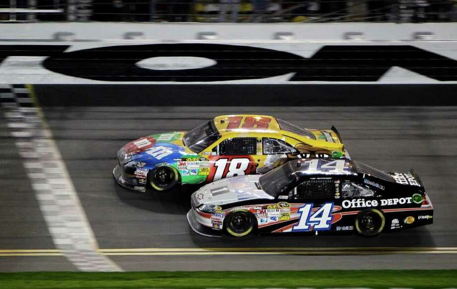 Kyle Busch (18), who used a slingshot pass on the last lap to beat defending champ Tony Stewart (14) to the finish line in the Budweiser Shootout, earned Toyota's first win in the event. Photo: AP