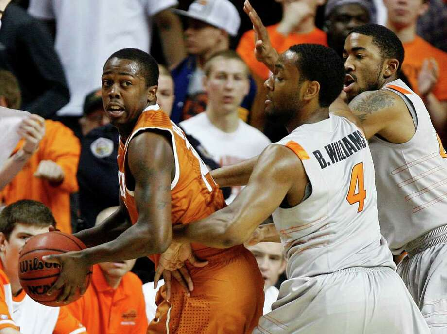 Texas' J'Covan Brown (14) looks to pass beside Oklahoma State's Brian Williams (4) and Michael Cobbins (20) during an NCAA college basketball game, Saturday, Feb. 18, 2012, in Stillwater, Okla. Oklahoma State won 90-78. (AP Photo/The Oklahoman, Bryan Terry) TABLOIDS OUT Photo: Bryan Terry, Associated Press / BRYAN TERRY/The Oklahoman