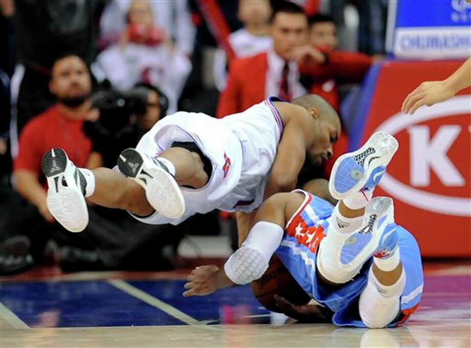San Antonio Spurs guard Gary Neal, left, and Los Angeles Clippers guard Randy Foye dive for a loose ball in the second half of an NBA basketball game, Saturday, Feb. 18, 2012, in Los Angeles. The Spurs won 103-100 in overtime. (AP Photo/Gus Ruelas) (AP)