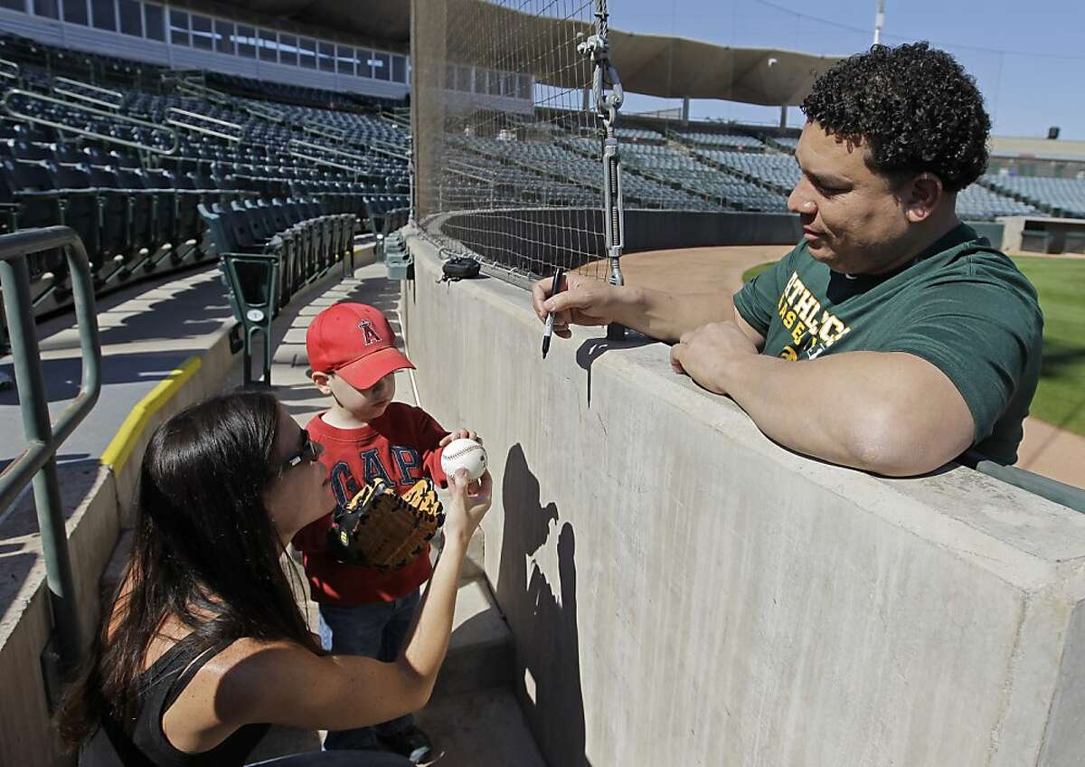 Oakland Athletics' Bartolo Colon signs an autograph for Mandy Vanek and her son, Brady, after arriving for spring training baseball, Saturday, Feb. 18, 2012 in Phoenix. (AP Photo/Darron Cummings)