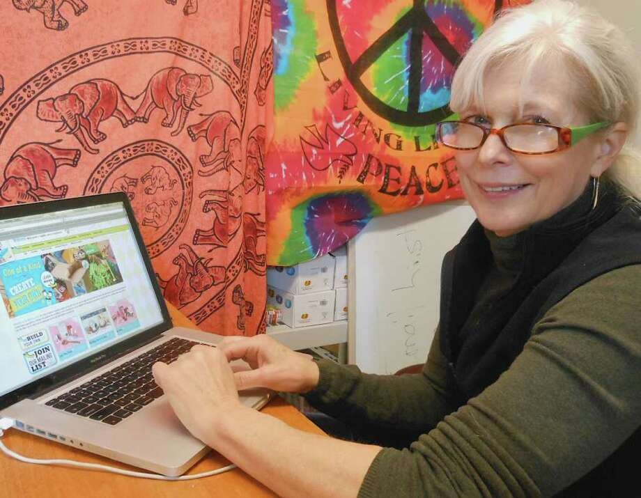 Fairfielder Gay Gasser with her laptop showing the web homepage of her new business, Mirth in a Box. Photo: Mike Lauterborn / Fairfield Citizen contributed