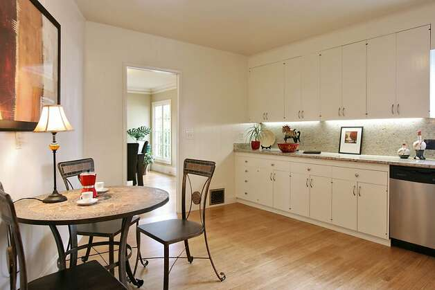 The cottage theme continues in the spacious, eat-in kitchen, where white cabinets are contrasted against the hardwood flooring, stone countertops and a natural-tile backsplash. Photo: Liz Rusby